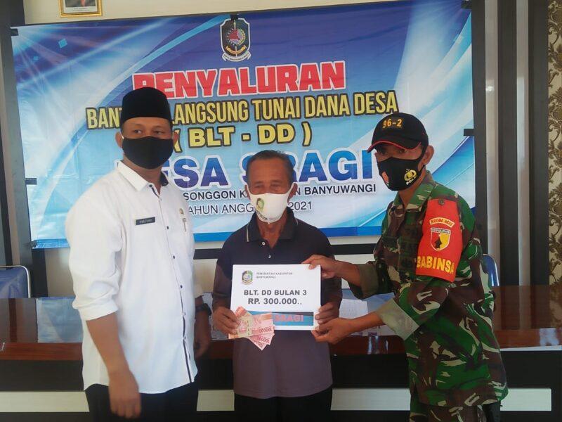 Anggota Babinsa Koramil 0825/20 Songgon melaksanakan kegiatan pengamanan penyaluran Bantuan Langsung Tunai (BLT) Dana Desa
