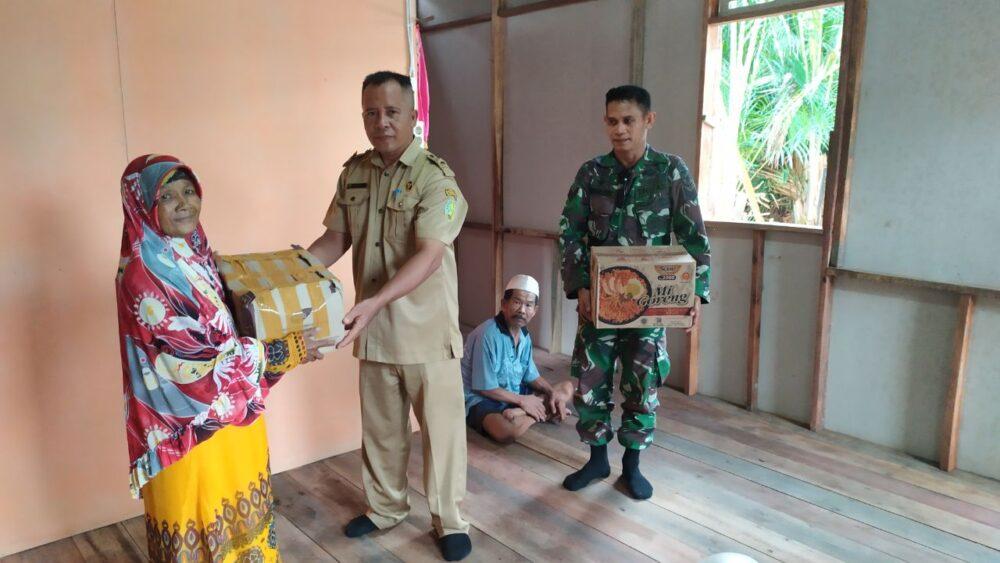 Sinergitas Babinsa Anggota Koramil 1208-06/Selakau bersama Kepala Desa (Kades) Bentunai menyerahkan bantuan sembako kepada warga