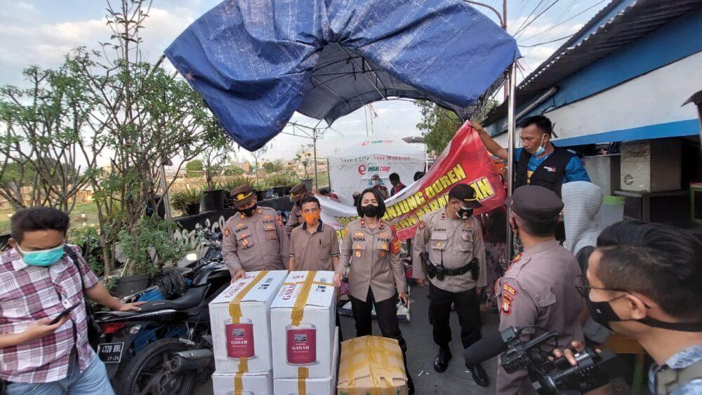 Anggota Polsek Tanjung Duren memberikan bantuan berupa baju bekas layak pakai kepada ratusan warga terdampak kebakaran di dua lokasi
