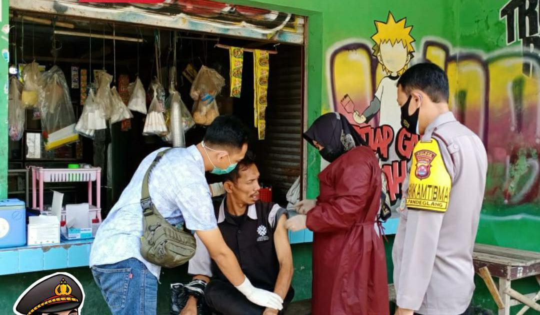 Bhabinkamtibmas Polsek Pandeglang Bripka Trimoyo mendampingi pelaksanakan vaksinasi secara door to door atau ke setiap rumah warga