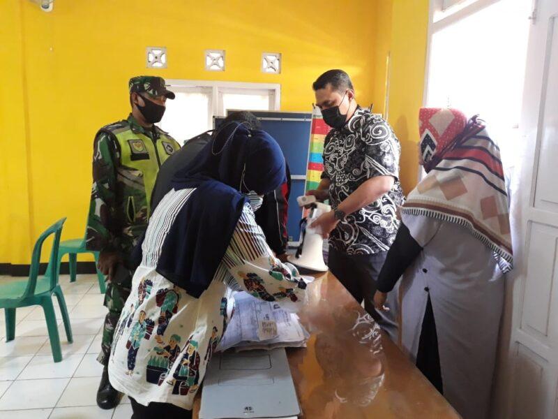 Kepala desa (Kades) Warnajati bersama istri memberikan himbauan kepada masyarakat agar tidak berkerumun saat pembagian kartu KKS